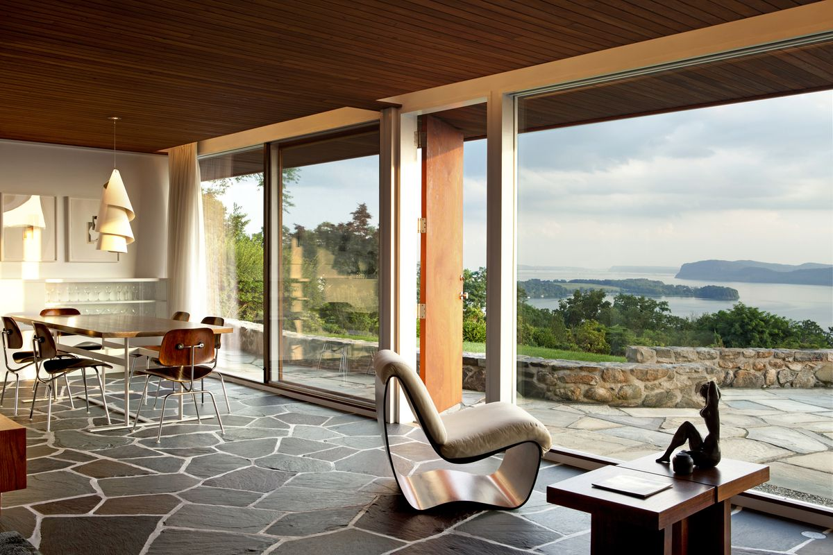 A living room has slate stone floors and floor-to-ceiling windows that look out onto a patio.