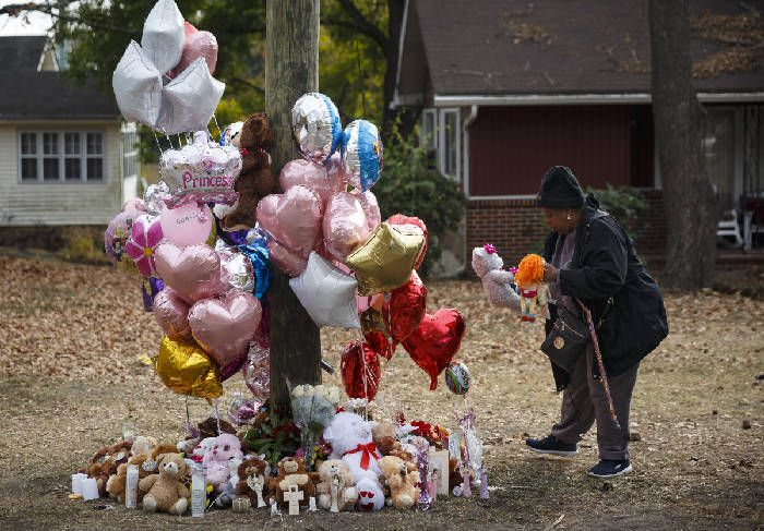 Neighborhood resident Michelle Ingram places a teddy bear in memory of victims at the site of the fatal school bus crash in Chattanooga.