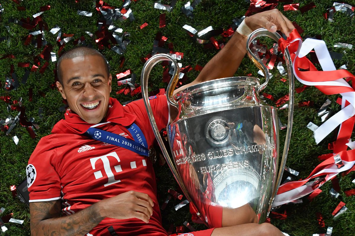 Paris Saint-Germain v Bayern Munich - UEFA Champions League Final - Thiago lies on ground with Champions League trophy, smiling, with confetti around him