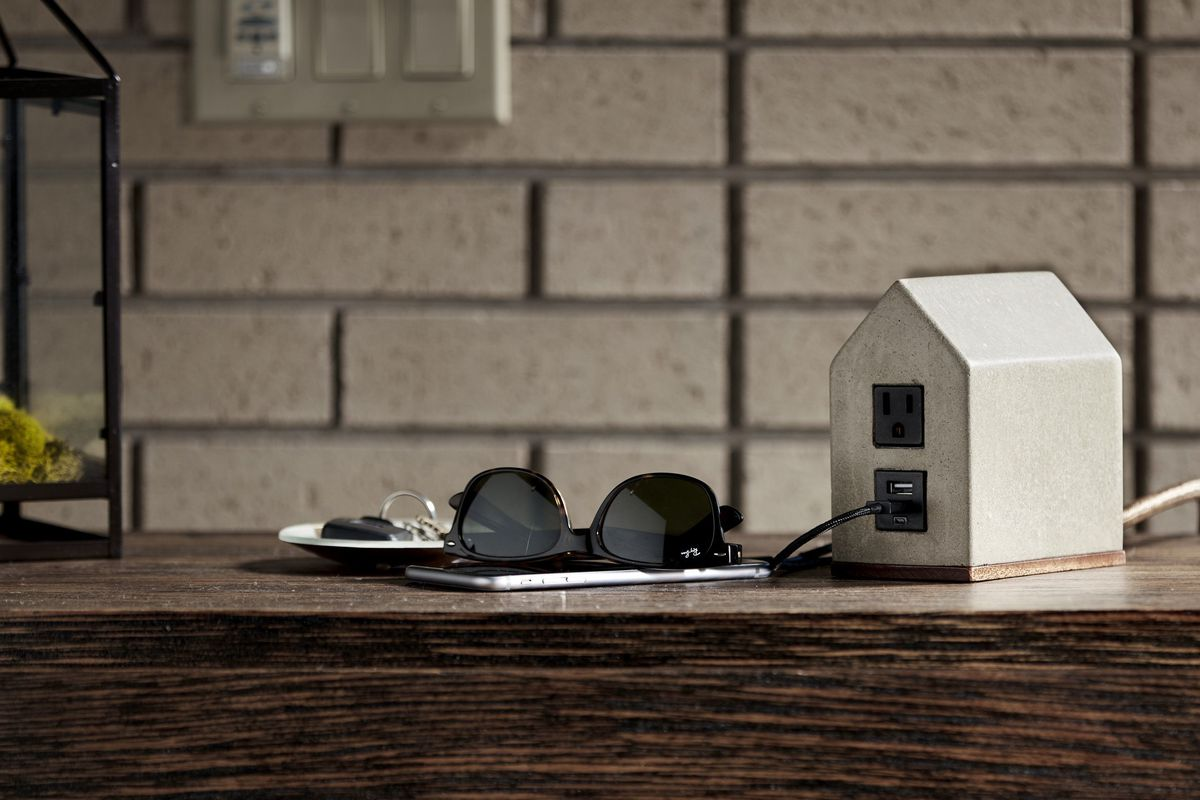 Small house-shaped outlet extension made from concrete on a table next to sunglasses and keys.