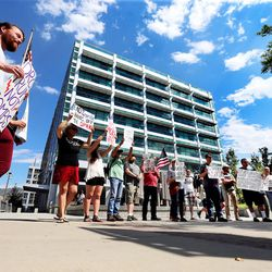 A small group of activists gathers at the Wallace F. Bennett Federal Building in Salt Lake City to protest President Donald Trump and war on Saturday, Aug. 19, 2017.