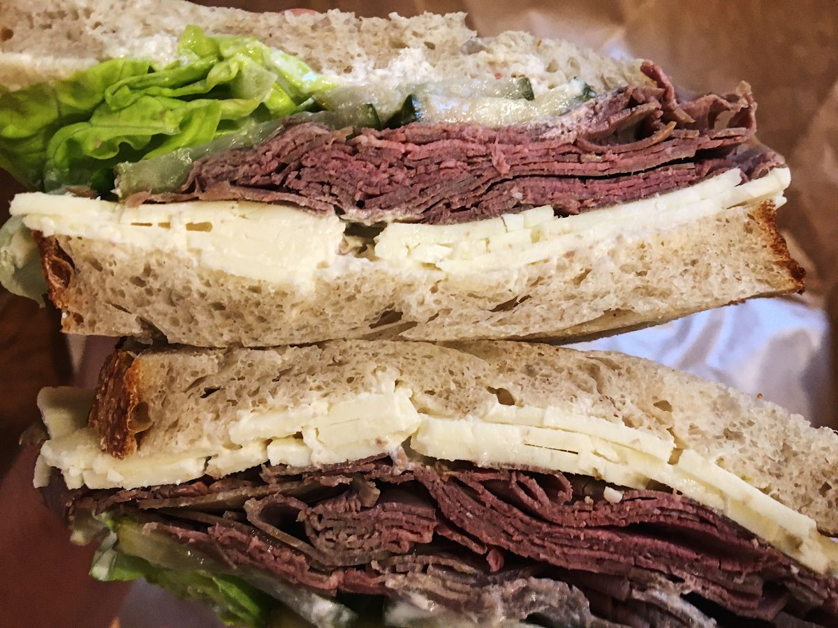 A roast beef sandwich on sliced bread with sliced cheese, lettuce, and pickles.