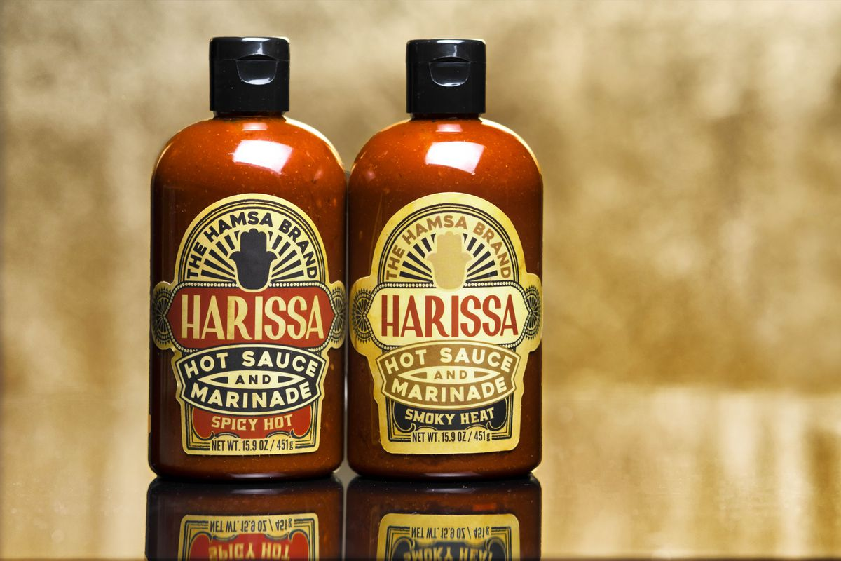 two bottles of deep-red-orange hot sauce with graphic labels featuring a hamsa hand.