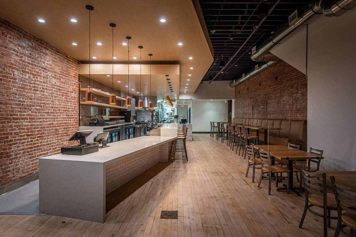 A long brick restaurant space with light wood floors.