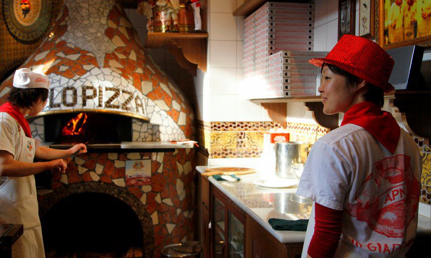 A cook fishes pizza out of a large pizza oven with flames visible within, while a server looks on with a prep station and pizza boxes stacked on a shelf in between