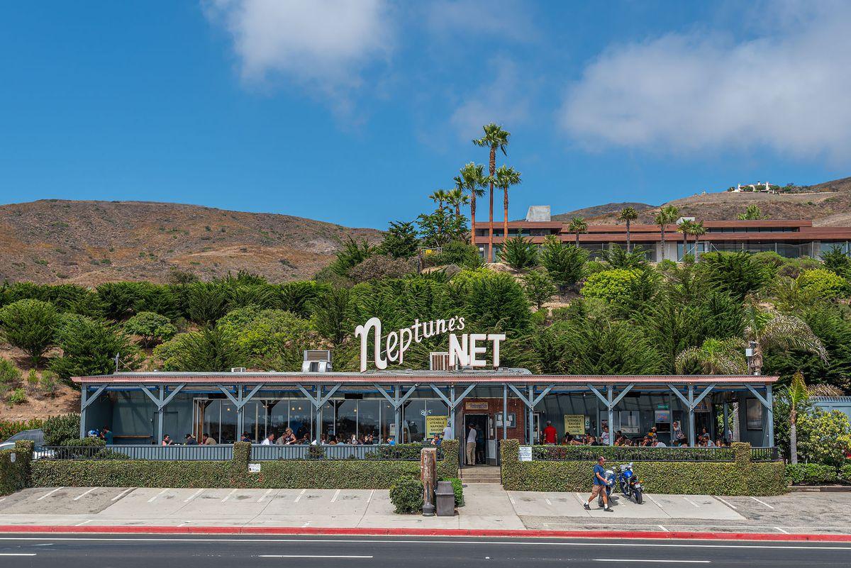 Malibu restaurant Neptune's Net, tucked against a brown hillside, as shown from the street.