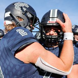 Corner Canyon's Jaxson Dart (2) hugs Charlie Ebeling (7) after the Chargers defeated Lone Peak 45-7 in the 6A football state championship game at Cedar Valley High School in Eagle Mountain on Friday, Nov. 20, 2020.
