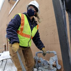 Kylie Hrubes, a Dominion Energy utility worker, is trained on how to replace a gas meter in West Valley City on Wednesday, Feb. 17, 2021.