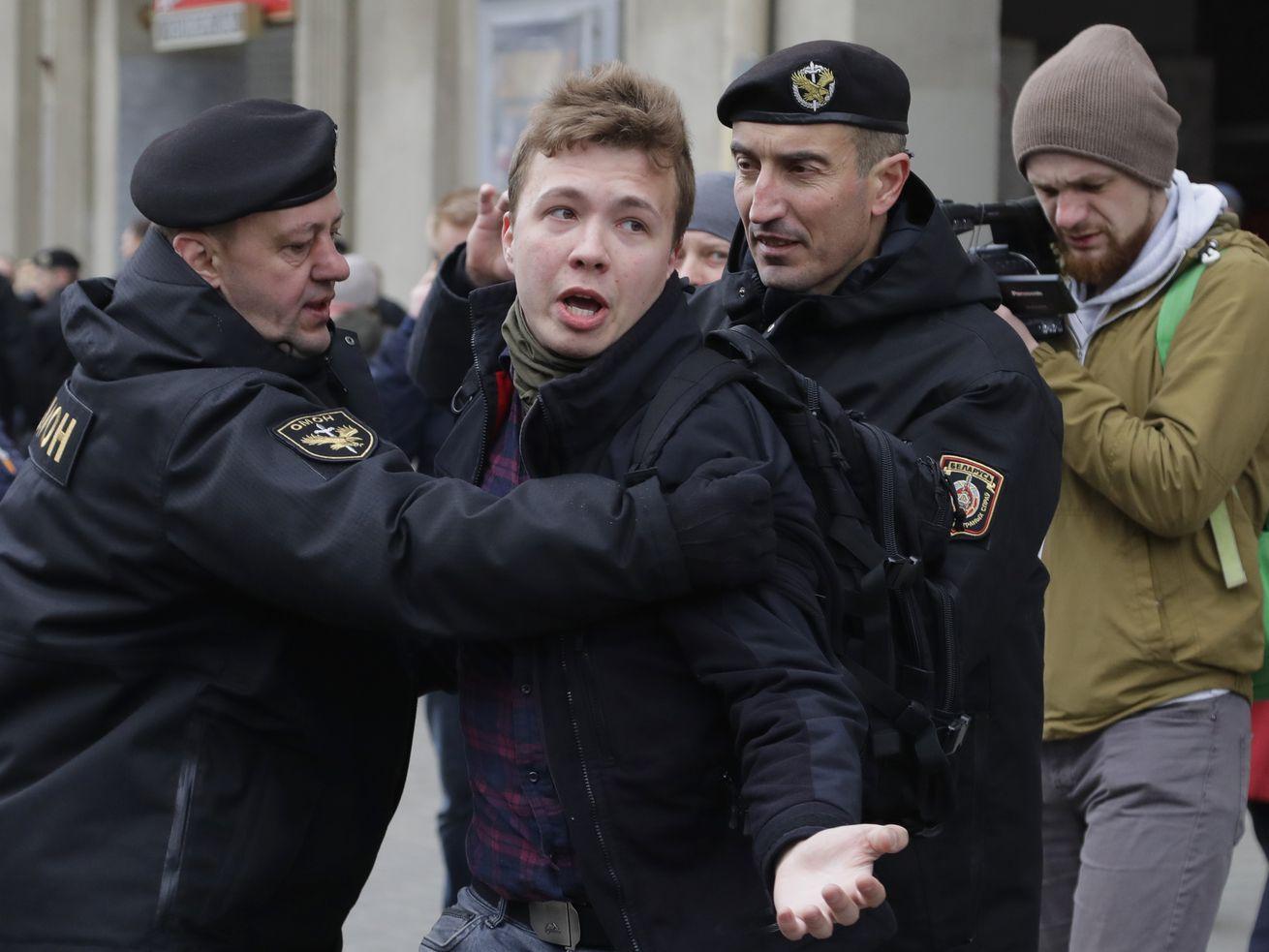 In this Sunday, March 26, 2017 file photo, Belarus police detain journalist Raman Pratasevich, center, in Minsk, Belarus.