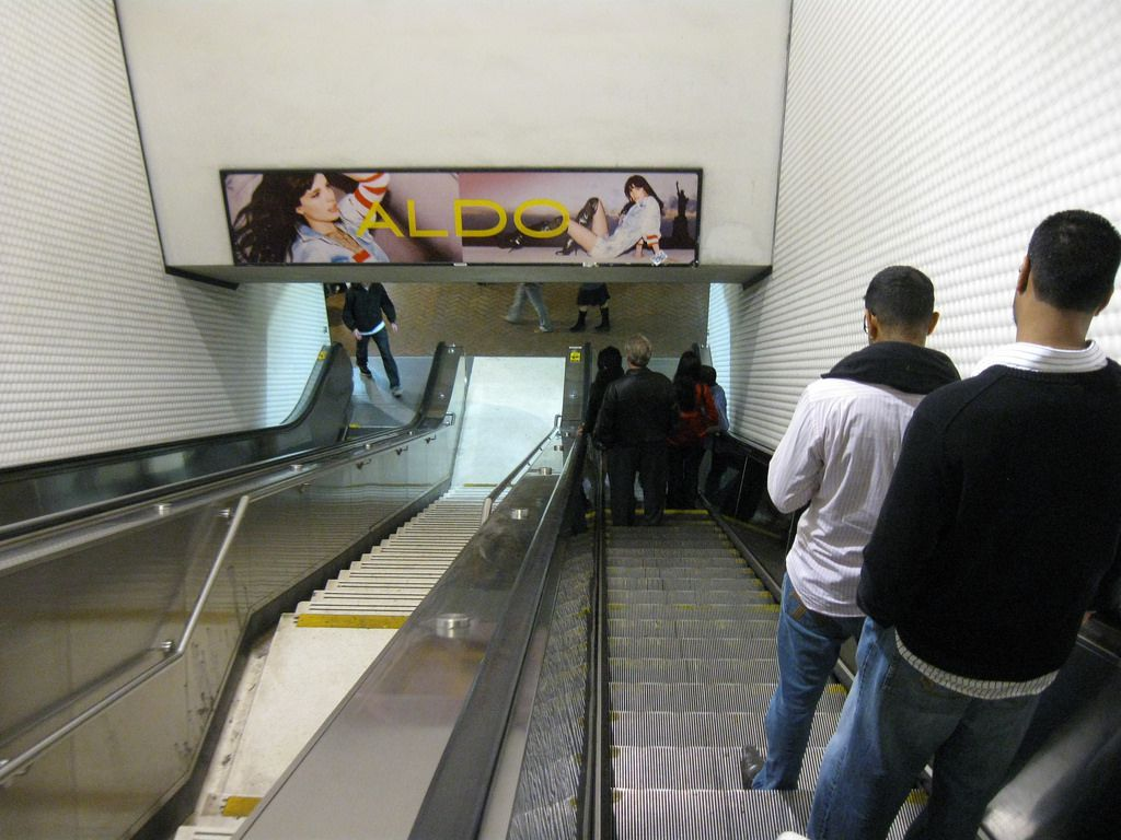 People descending the escalator at Powell Street BART station.