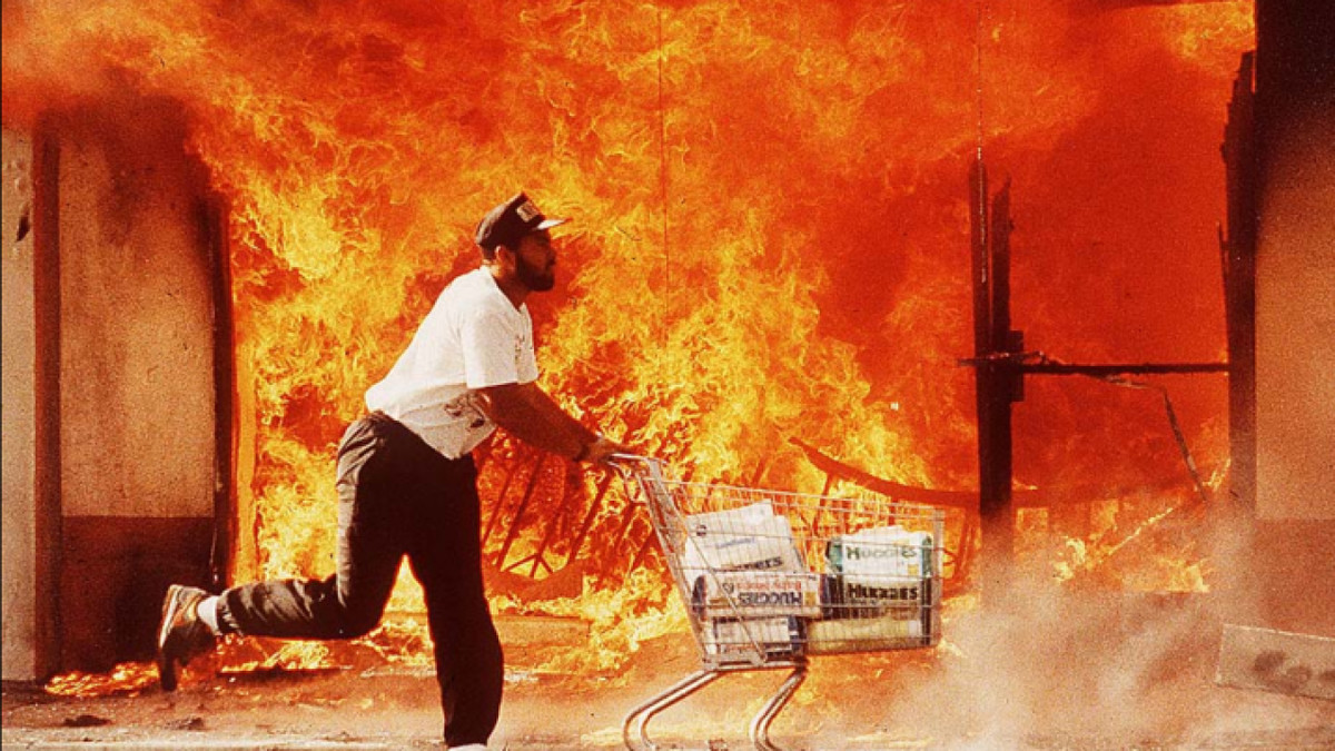 A man pushes a shopping cart in front of a burning building.