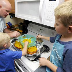 Kelly Burton makes pumpkin pie from scratch and gets help scooping pumpkin from 3-year-old Logan, center, and 6-year-old Porter on Sept. 25.