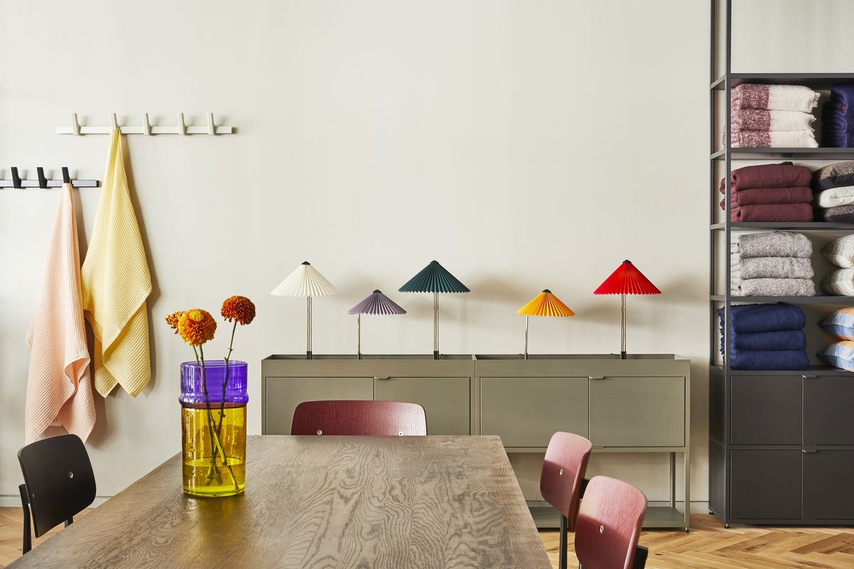 A wooden table with a colorful vase and flowers. Behind it is a row of multicolored lamps and stacked of towels.