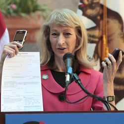 Secretary of State Debra Bowen displays cellphones and a paper form to demonstrate the different ways California voters register to vote during a news conference Wednesday, Sept. 19, 2012,  in Sacramento, Calif.  California launched a new online voter registration system  that will be checked  against their driver's license or the state identification card.
