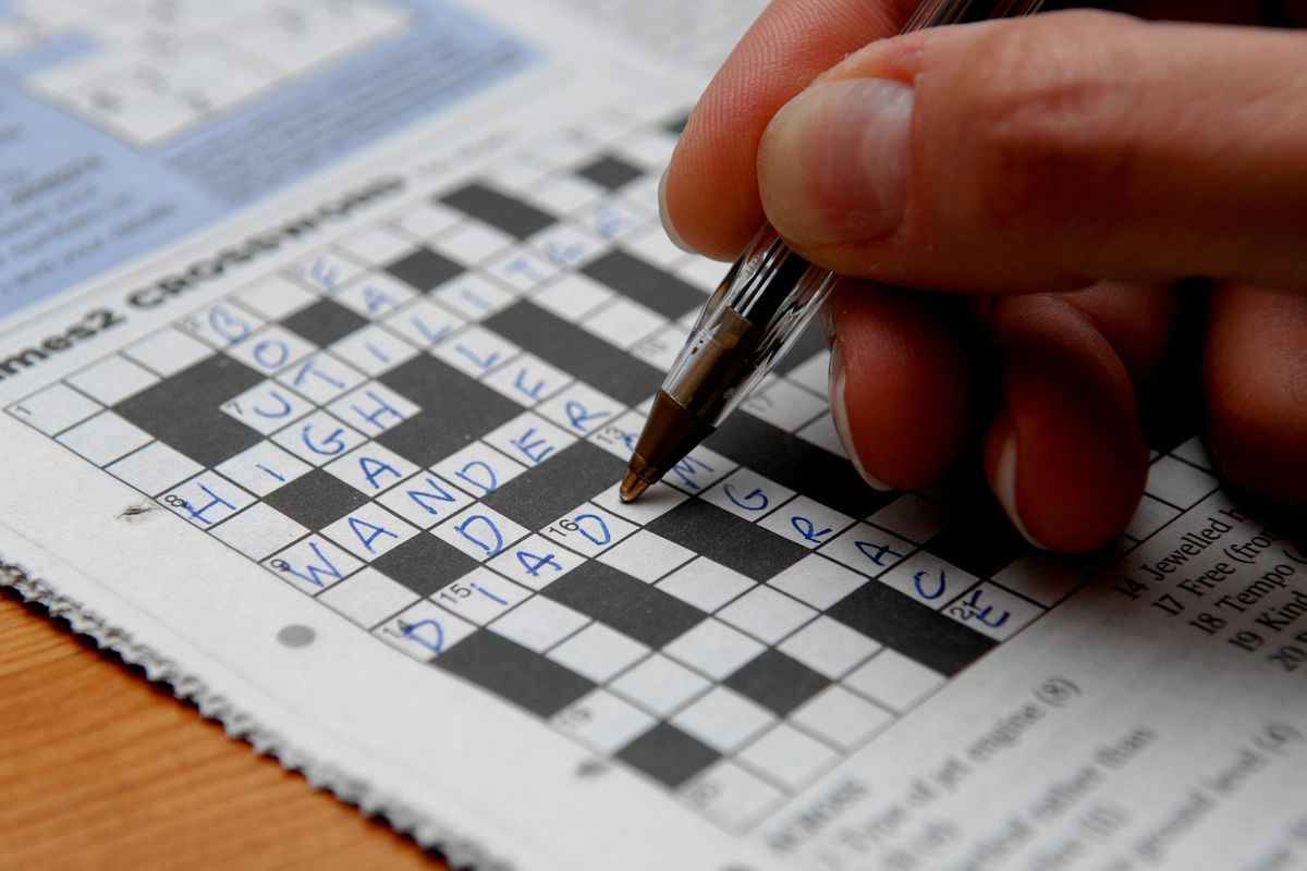 Photo of a crossword puzzle being completed by a hand holding a pen.