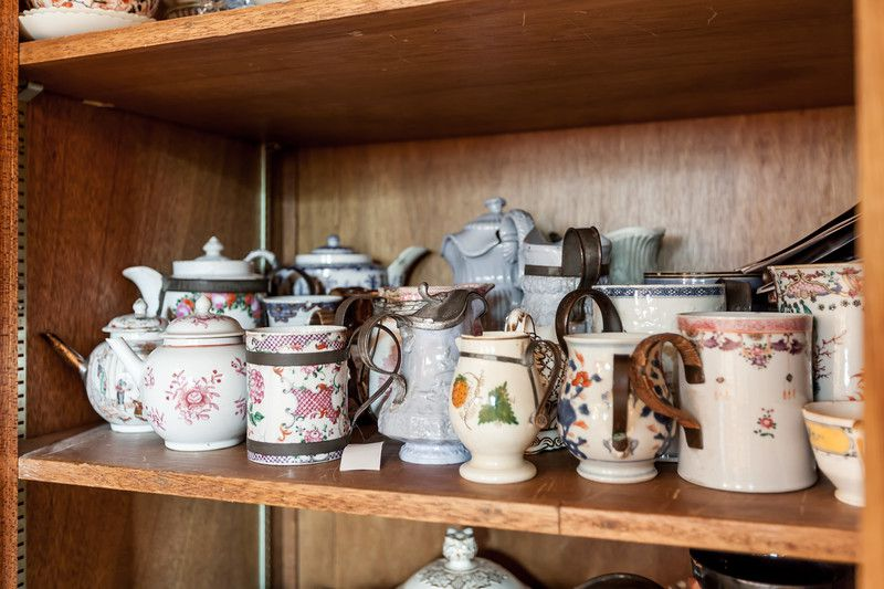A shelf with multiple mugs, cups, and pitchers.