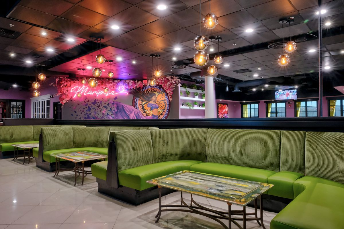 A lounge with green couches and neon