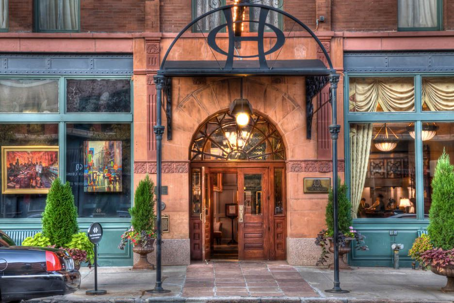 The exterior of the Oxford Hotel in Denver. There is a large arched doorway. There is an awning over the doorway with the letters O and H.
