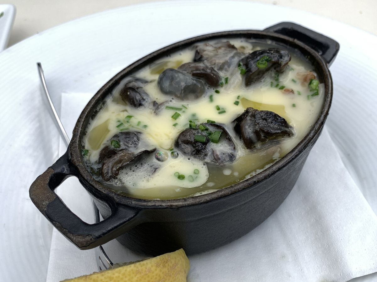A pot of escargots on a plate on a white tablecloth