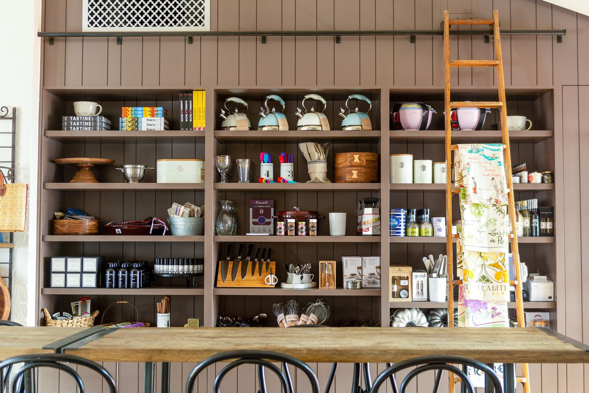 A rustic cooking school offers shelves of cooking equipment for sale.