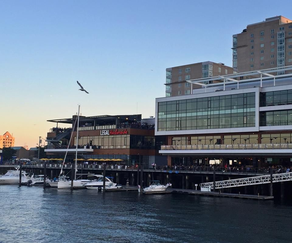A waterfront view of Legal Harborside at dusk, with a final bit of sun peeking over the horizon.