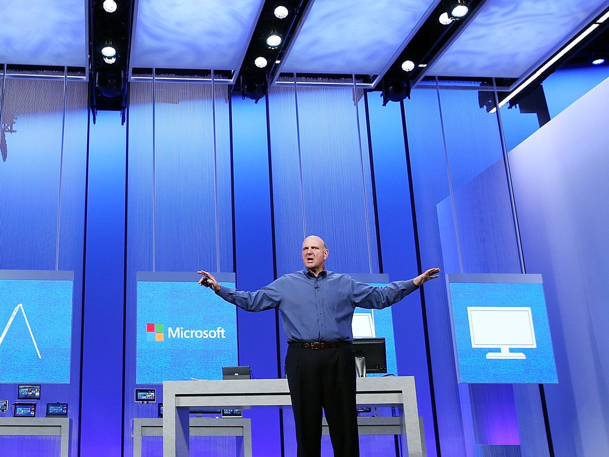 A man in a blue shirt and black pants stands on a stage with his arms outstretched. Behind him are multiple posters. One of the posters has a word which reads: Microsoft.