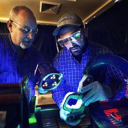 Instructor Kent Hornbeck, left, and student Craig Perkins use a black light to inspect grips for ski resort chairlifts at Salt Lake Community College's Westpointe Center in Salt Lake City on Wednesday, Dec. 9, 2015.