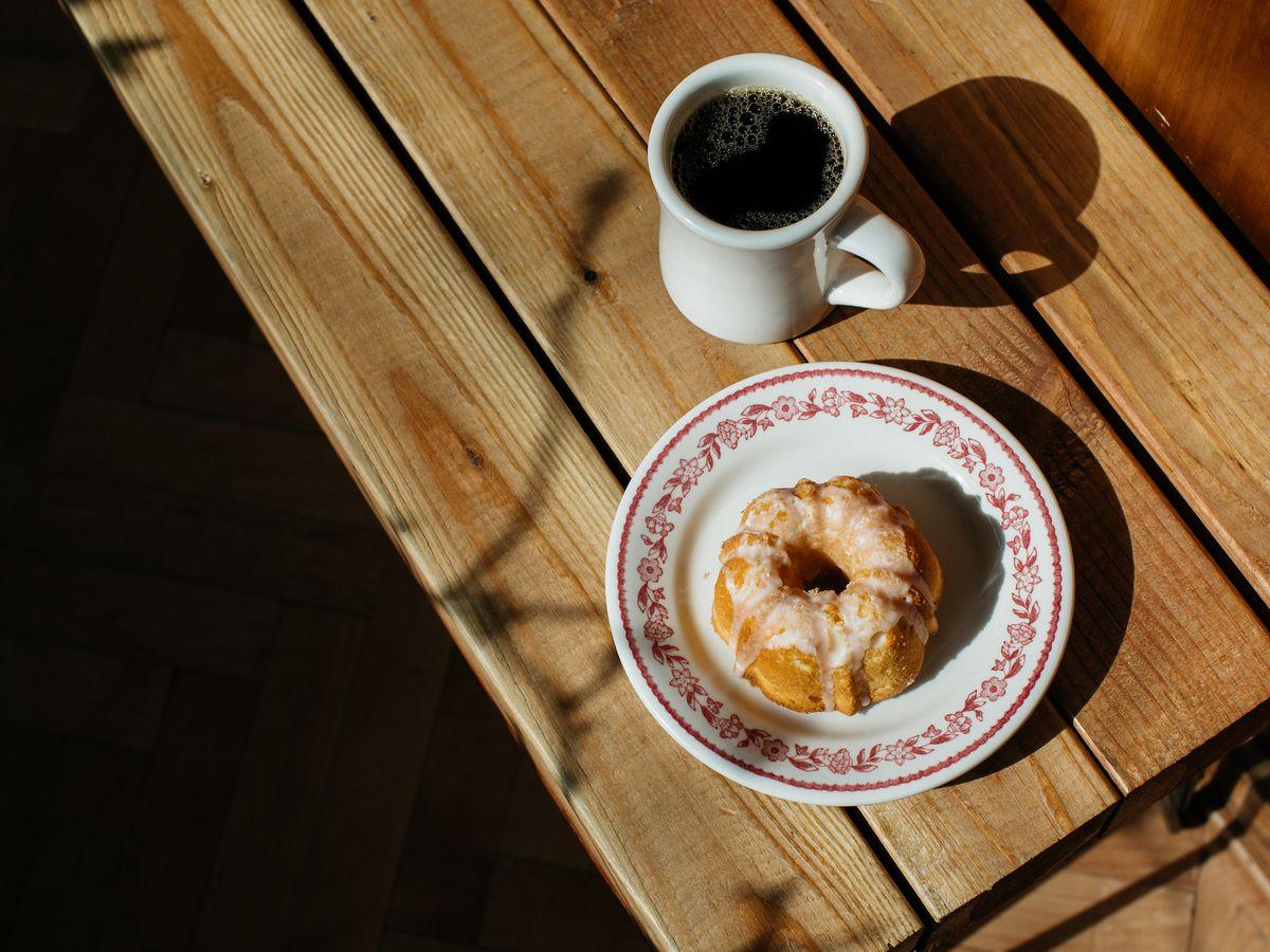 A white mug of coffee sits next to a mini bundt cake on a pink and white china plate.