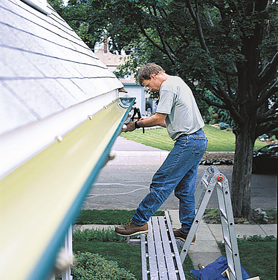 Man Installing Gutter On House