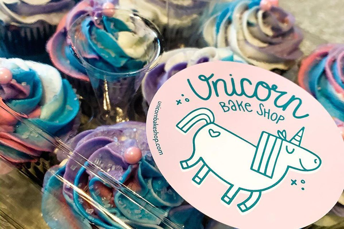 """A plastic clamshell cupcake box is filled with teal, pink, and white frosted cupcakes, with a pink and white """"unicorn bake shop"""" label"""