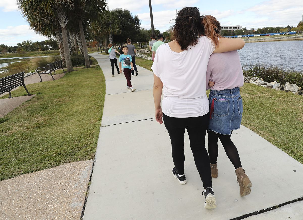 Heather Wakefield hugs her daughter Kelsie as the family walks at Kissimmee Lakefront Park in Kissimmee, Fla., on Monday Dec 21, 2020.