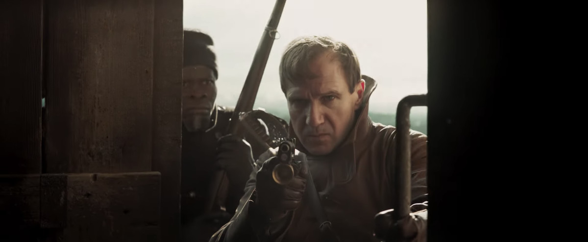 Two men, both armed with weapons, peer through a door in The King's Man