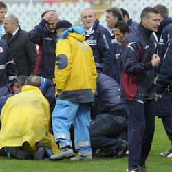 Medics assists Livorno's Piermario Morosini, not shown,  as he lies on the turf of the Pescara's Adriatico stadium, central Italy, Saturday, April 14, 2012, during a Serie B soccer match between Pescara and Livorno. Morosini, who was on loan from Udinese, fell to the ground in the 31st minute of the match and received urgent medical attention on the pitch. A defibrillator was also used on the 25-year-old, who was later confirmed top have died. The match was called off, with the other players leaving the field in tears.