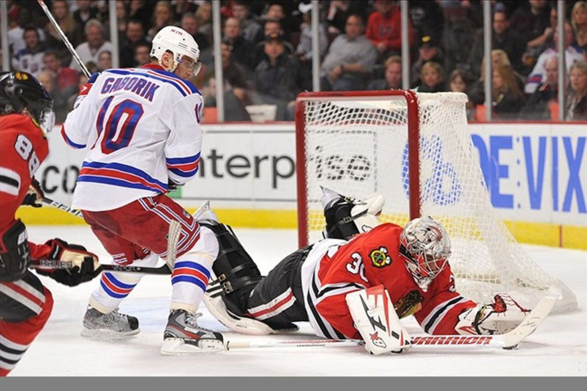 Mar 9, 2012; Chicago, IL, USA; Chicago Blackhawks goalie Ray Emery (30) covers the puck in front of New York Rangers right wing Marian Gaborik (10) during the first period at the United Center. Mandatory Credit: Rob Grabowski-US PRESSWIRE