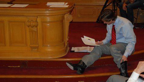 Sen. Mike Johnston studies a document during Senate Bill 13-213 testimony.