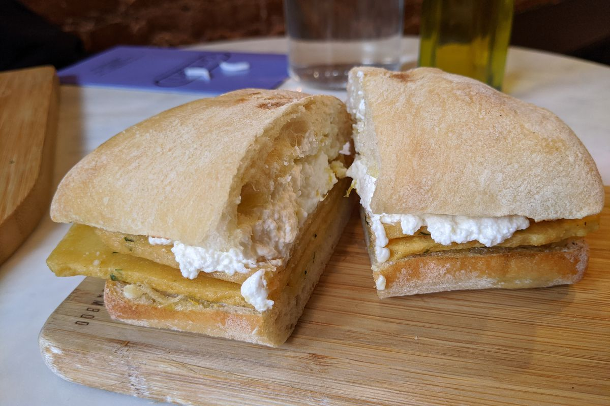 A sandwich of yellow slabs of fried chickpea paste and ricotta cheese.
