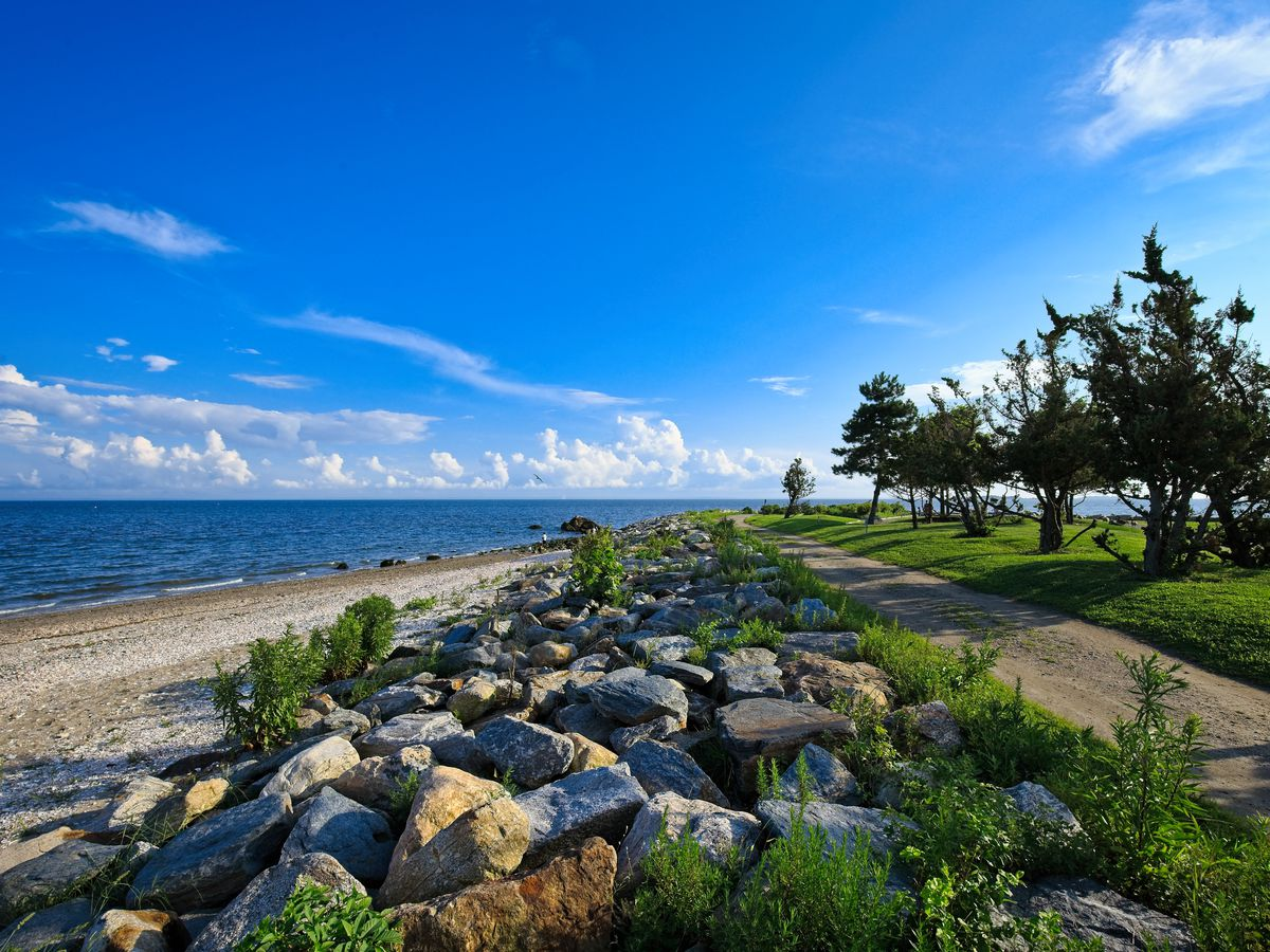 In the foreground are rocks and a path. The rocks border a sandy beach which borders a body of water. There are trees in the distance.