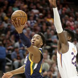 Utah Jazz guard Donovan Mitchell (45) shoots in front of Phoenix Suns center Deandre Ayton (22) during an NBA game at the Vivint Smart Home Arena in Salt Lake City on Monday, Feb. 24, 2020.