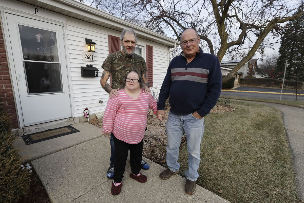 Tyrone Cefalu (right), Robert Goldberg and his sister Debbie Goldberg in front of Robert Goldberg's home in suburban Chicago.