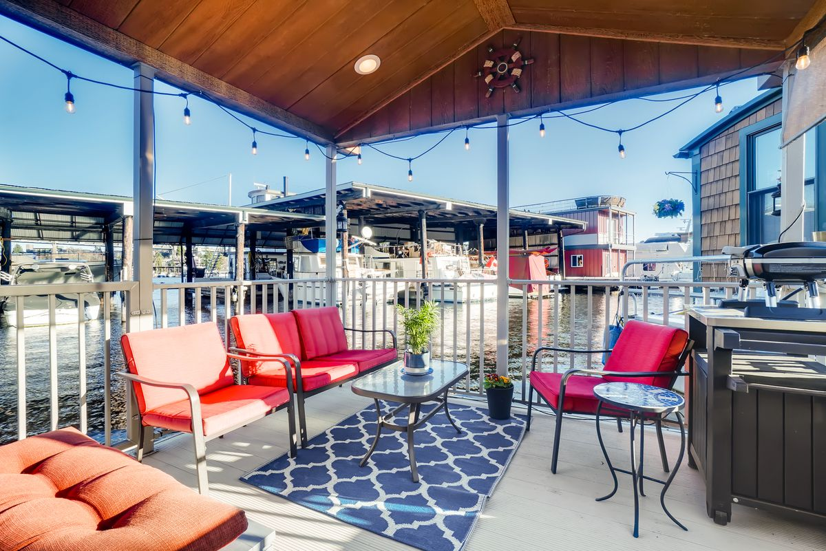 A covered deck features red seating, a coffee table, twinkle lights, and a grill.