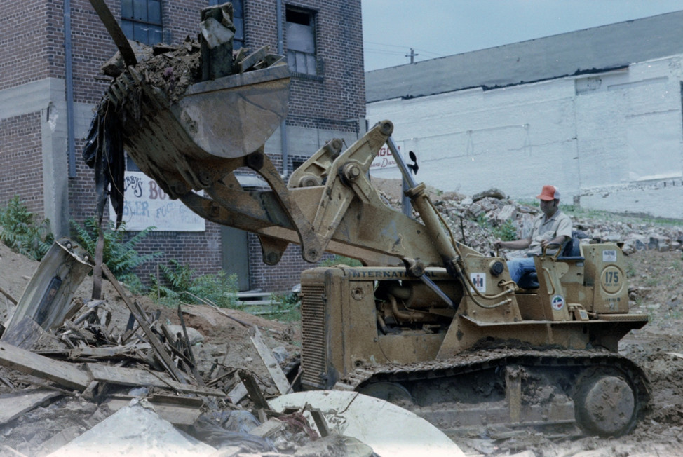 A man on a backhoe removes giant amounts of dirt and grime.