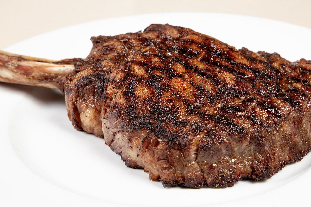 a bone-in steak with grill marks on a white plate