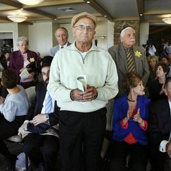 Holocaust survivor Abe Katz, front, stands to be recognized during a Utah Holocaust Memorial Commemoration at the Jewish Community Center in Salt Lake City, Thursday, April 19, 2012.