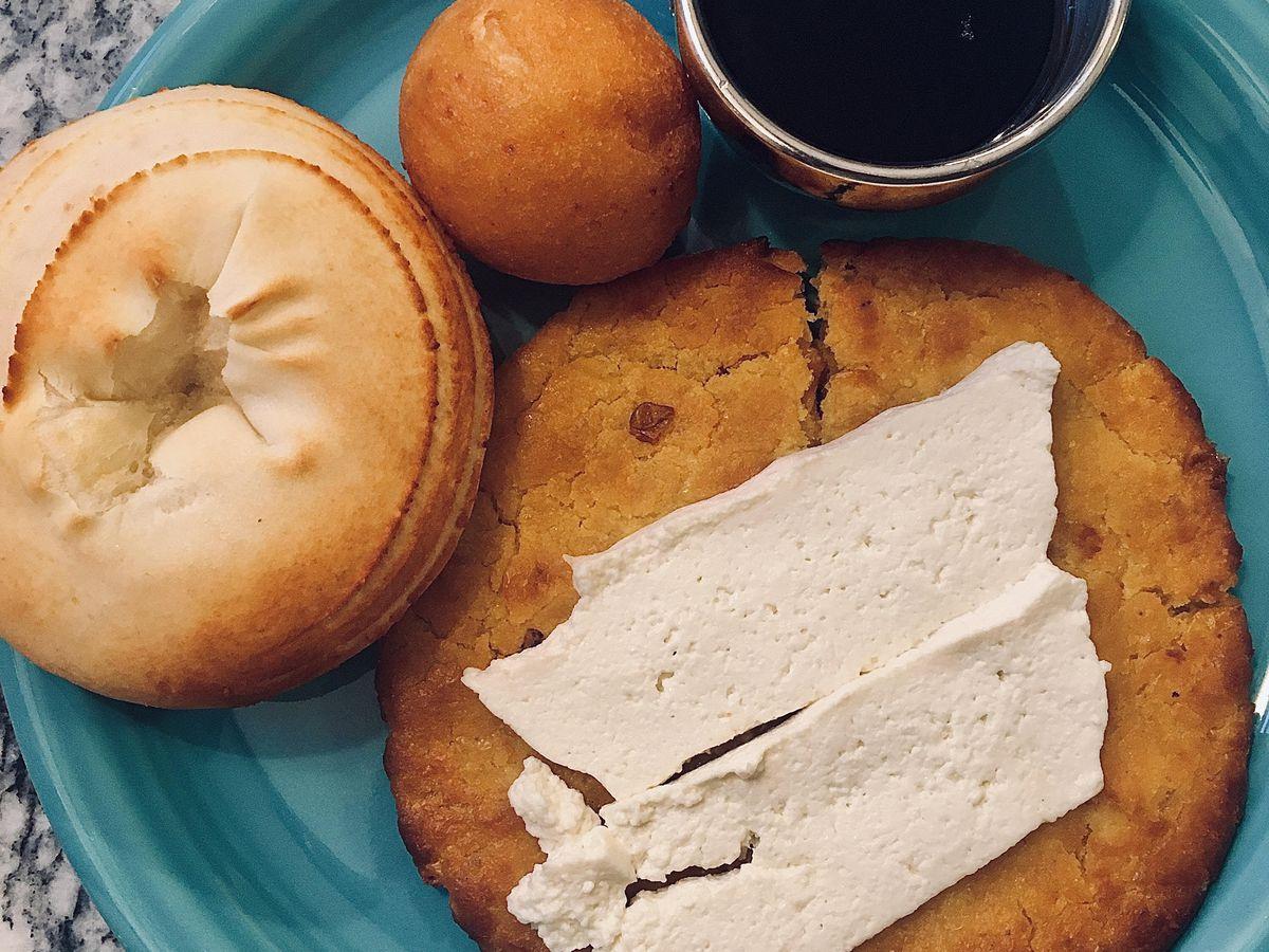 Various Colombian breads wit on a blue plate atop a granite counter, adjacent a cup of coffee