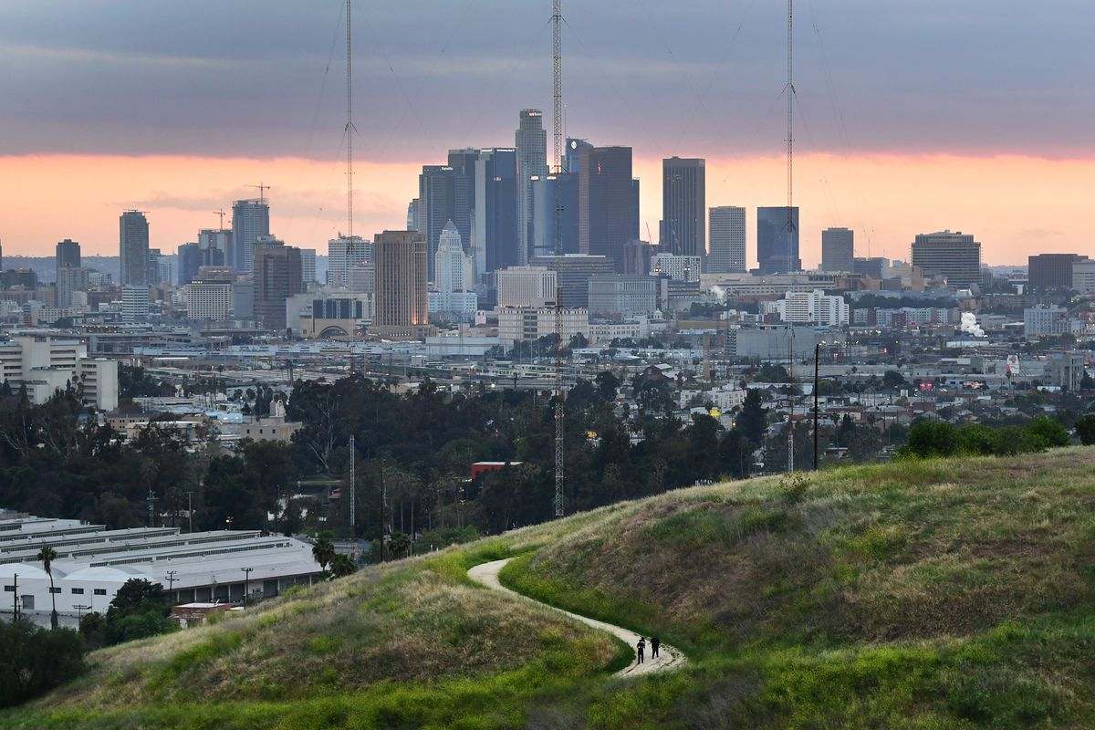 Hikers walk on a trail with a view of the Los Angeles city skyline in Los Angeles on April 20, 2020.