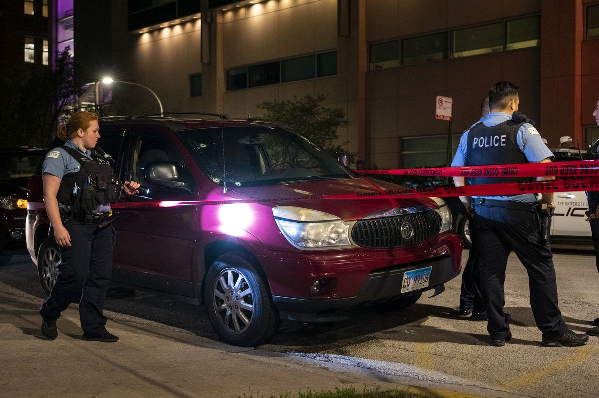 Chicago police guard a red SUV outside Comer Children's Hospital that was involved in a shooting where at least 7 people were shot in the 6600 block of South Halsted Street, in the Englewood neighborhood neighborhood, Thursday, July 1, 2021.
