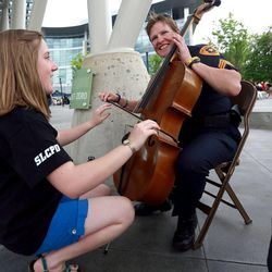 Melinda Pehrson helps Salt Lake Police Sgt. Lisa Pascadlo play the cello at Five-O Fest, a free community festival hosted by the Utah Anti-Bullying Coalition, Safe2Help and the Salt Lake City Police Foundation outside of the Public Safety Building in Salt Lake City on Saturday, May 31, 2014.