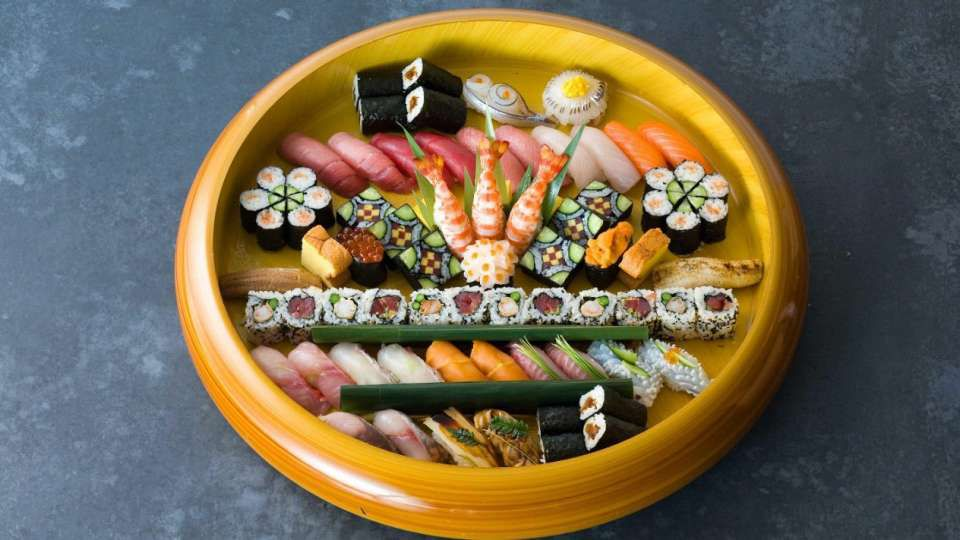 Round yellow dish containing spread of sushi