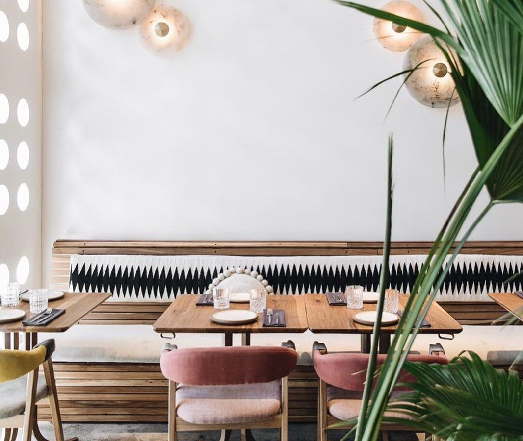 Tables, seats, and decorative banquette against a tall white wall accented with seashell like sconces