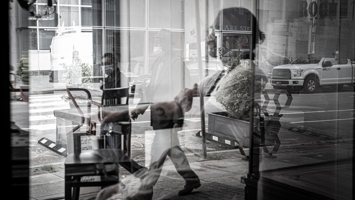 Chef Sunny Gerhart sits alone in the glass windows at the entrance  of his restaurant, St., Roch, in downtown Raleigh